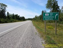 HWY 17 #1338 - © Cameron Bevers: A close-up view of a green highway guide sign which reads, Hwy 11 East/Est Greenstone Cochrane