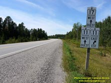 HWY 17 #1339 - © Cameron Bevers: A close-up view of a white highway junction sign assembly at Hwy 11 and Hwy 17 with cardinal directions and arrows shown