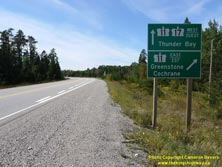 HWY 17 #1341 - © Cameron Bevers: A close-up view of two green highway guide signs, which read Hwy 11 Hwy 17 West/Ouest Thunder Bay and Hwy 11 East/Est Greenstone Cochrane