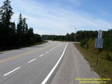 HWY 17 #1342 - © Cameron Bevers: A close-up view of a white highway junction sign assembly at Hwy 11 and Hwy 17 with cardinal directions and arrows shown