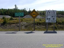 HWY 17 #1347 - © Cameron Bevers: A close-up view of the oversized white highway junction signs for Hwy 11 and Hwy 17 with cardinal directions and arrows shown, along with fingerboard destination guide signs reading Sault Ste Marie 577 (km) and Thunder Bay 110 (km) and a road-end checkerboard sign