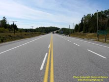 HWY 17 #1351 - © Cameron Bevers: A centreline view of Hwy 11 and Hwy 17 with two green highway guide signs at right, which read Railway Street and Business Section