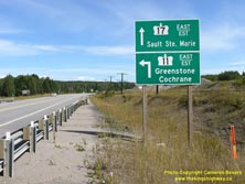 HWY 17 #1352 - © Cameron Bevers: A close-up view of two green highway guide signs, which read Hwy 17 East/Est Sault Ste Marie and Hwy 11 East/Est Greenstone Cochrane