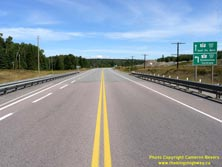 HWY 17 #1353 - © Cameron Bevers: A centreline view of Hwy 11 and Hwy 17 with two green highway guide signs at right, which read Hwy 17 East/Est Sault Ste Marie and Hwy 11 East/Est Greenstone Cochrane