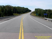 HWY 17 #1365 - © Cameron Bevers: A centreline view of Hwy 11 and Hwy 17 with a blue municipality sign at right, which reads Nipigon Population 1800 along with three green highway guide signs, which read Railway Street Business Section and Landing Road