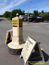 HWY 17 #1370 - © Cameron Bevers: A close-up view of a beige-and-yellow painted concrete traffic pylon within an intersection with a commercial building in the background