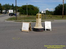 HWY 17 #1371 - © Cameron Bevers: A close-up view of a beige-and-yellow painted concrete traffic pylon within an intersection