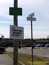 HWY 17 #1372 - © Cameron Bevers: A close-up view of a green street sign, reading To Hwy 11-17 West with a commercial plaza in the background