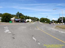 HWY 17 #1373 - © Cameron Bevers: An off-centreline view of Old Hwy 17 with a commercial building at left and a concrete traffic pylon within the intersection at right