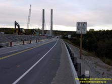 HWY 17 #1380 - © Cameron Bevers: A close-up view of a white highway junction sign assembly at Hwy 11 and Hwy 17 with cardinal directions and arrows shown. The new cable-stayed bridge over the Nipigon River is visible at left along with various construction equipment and barrels.