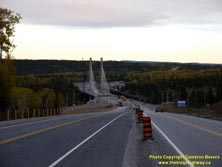 HWY 17 #1382 - © Cameron Bevers: A view of the approach to the cable-stayed bridge over the Nipigon River on Hwy 11 and Hwy 17 while it was under construction from the future highway centreline. In the background, the new bridge is partially-completed at left while the existing bridge is at right. Various traffic signs and construction barrels are visible.