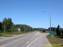 HWY 17 #1387 - © Cameron Bevers: An angled side view of Hwy 11 and Hwy 17 approaching an intersection with three green highway guide signs at right, reading First Street Business Section and Ministry of Natural Resources